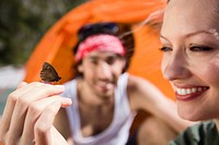 Germany, Bavaria, Young couple camping, butterfly resting on woman's hand