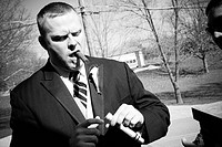 groom holding, smoking a cigar