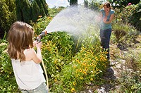 Girl spraying water at mother
