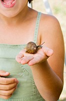 Child holding a snail
