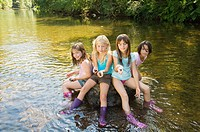 Girls in a river with rocks