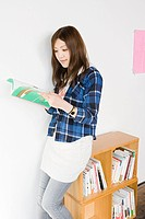 Young woman looking at design book (thumbnail)