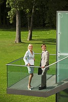 Germany, business people standing on staircase, park in background