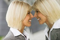 Germany, businesswoman looking at mirror image