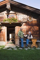 Austria, Karwendel, Senior couple in front of log cabin, holding mugs