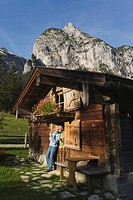 Austria, Karwendel, Senior couple leaning on log cabin