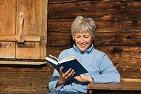 Austria, Senior woman reading book, sitting at log cabin