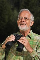 Austria, Karwendel, Senior man holding binocular, portrait