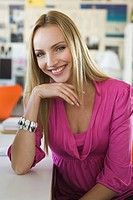 Young woman in office, smiling, portrait