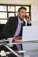Business man in office using mobile phone, portrait