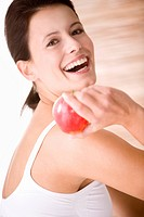 Young woman holding an apple, laughing, close up