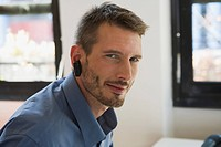 Business man in office wearing headset, portrait