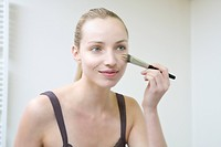 Young woman using make_up brush, portrait