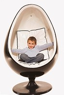 Little boy 4_5 relaxing in design chair, smiling