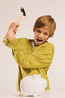 Teenage boy 13_14 brandishing hammer, piggy bank in foreground