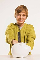 Teenage boy 13_14 holding hammer, piggy bank in foreground
