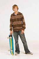 Teenage boy 13_14 standing with skateboard over head, smiling