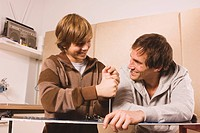 Germany, father and son fixing snowboard, smiling