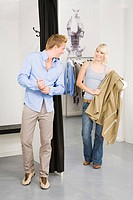 Young man in changing room, woman in background holding jacket