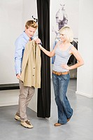 Young couple in changing room, man holding jacket