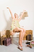 Young woman in shoe shop, holding shopping bag, rejoicing