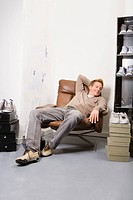 Young man in shoe store, relaxing
