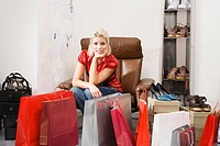 Young woman in shoe shop, shopping bags in foreground
