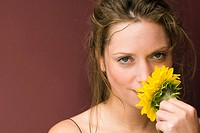 Young woman holding sunflower, portrait, close up