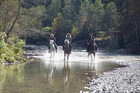 Austria, Salzburger Land, Altenmarkt, Young people riding horses across river