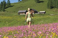 Austria, Salzburger Land, Young woman, Nordic walking, rear view