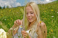 Austria, Salzburger Land, Altenmarkt, Young woman plucking petals from flower, smiling, portrait