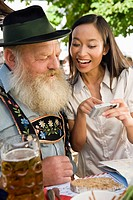 Germany, Bavaria, Upper Bavaria, Bavarian man and Asian woman in beer garden, close_up