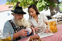 Germany, Bavaria, Upper Bavaria, Asian woman and Bavarian man in beer garden