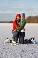 Austria, Salzkammergut, Lake Irrsee, Female teenagers 14_15 on skates, embracing