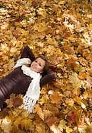 Austria, Female teenager 14_15, relaxing on leaves portrait, elevated view