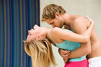 Man kissing a woman on her neckline