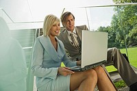 Germany, two business people using laptop