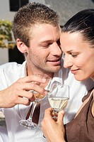 Young couple flirting, holding wine glasses, close_up