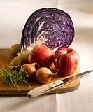 Red cabbage, apples, potatoes, thyme and onions on chopping board