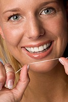 Young woman flossing her teeth, portrait, close_up