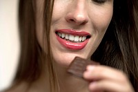 Young woman holding chocolate candy, portrait