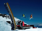 Skiers jumping piste machine