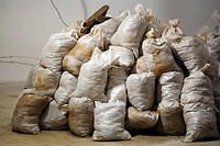 Stack of white construction bags filled with soil