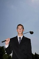 Man in business suit holding golf club