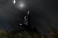 a businessman throwing documents into the night sky, with the moon lighting the sky behind him.