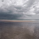 storm clouds hang over a beach at low tide
