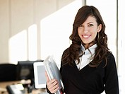 Portrait of young business woman smiling, standing near desks, folder in hands