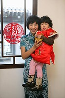 Chinese mother holding her daughter looking at camera smiling