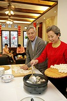 Chinese mature couple making Chinese dumpling on New Year´s Eve