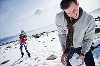 Woman throwing snowball at man